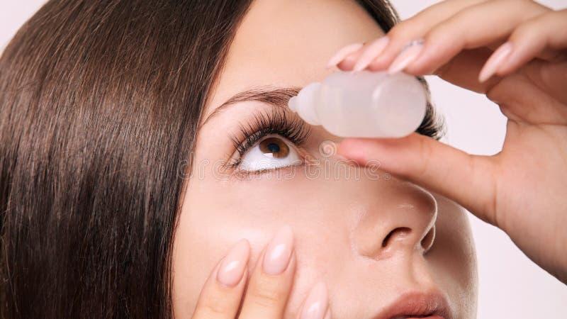 Женщина прикладывает падения глаза Обработка глаукомы девушки стоковые изображения