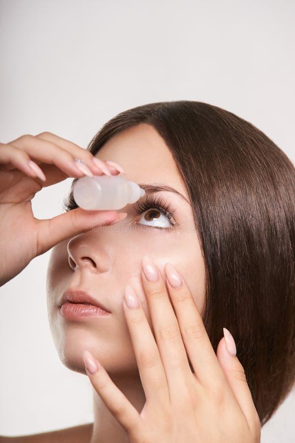 Женщина прикладывает падения глаза Обработка глаукомы девушки стоковые фотографии rf
