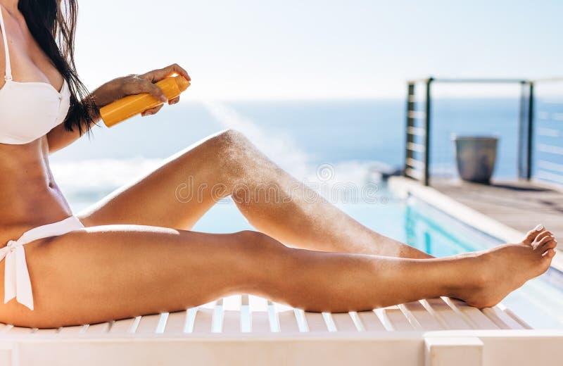 Женщина прикладывая брызги suntan стоковые фотографии rf