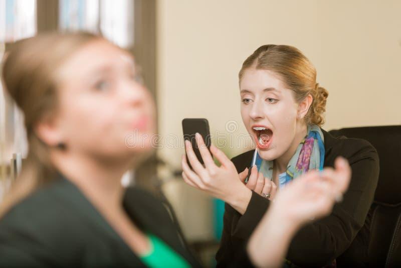 Женщина прикладывая макияж используя ее телефон как зеркало стоковые фотографии rf