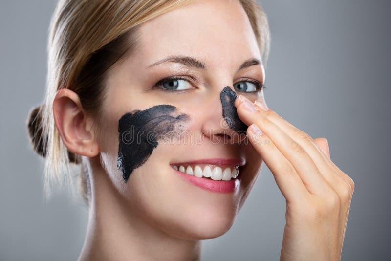 Женщина прикладывая маску активированного угля на ее стороне стоковое фото rf