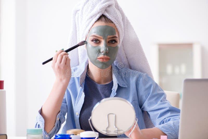 Женщина прикладывая маску глины с щеткой дома стоковая фотография rf