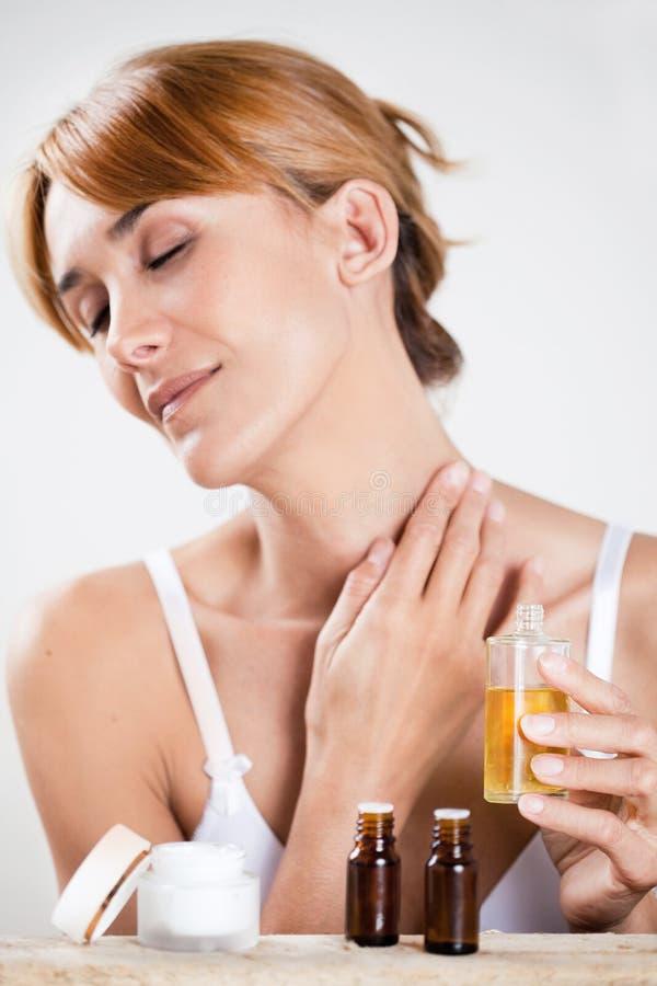Женщина прикладывая масло стоковое фото rf
