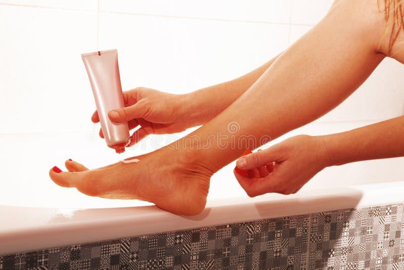 Женщина прикладывая сливк ноги стоковые фотографии rf