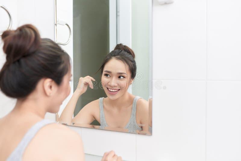 Женщина прикладывая сливк стороны после ежедневного ливня Делать ежедневный режим утра в bathroom стоковые фотографии rf