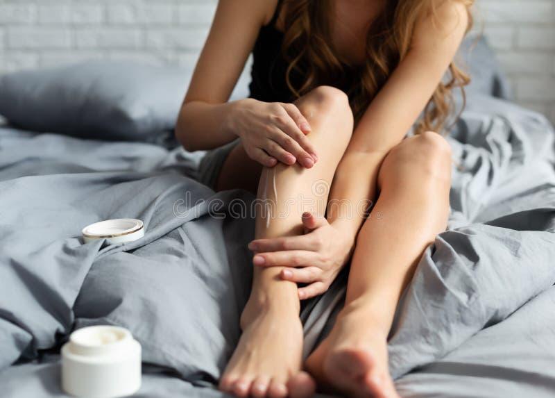 Женщина прикладывая сливк тела на ее ноге стоковая фотография