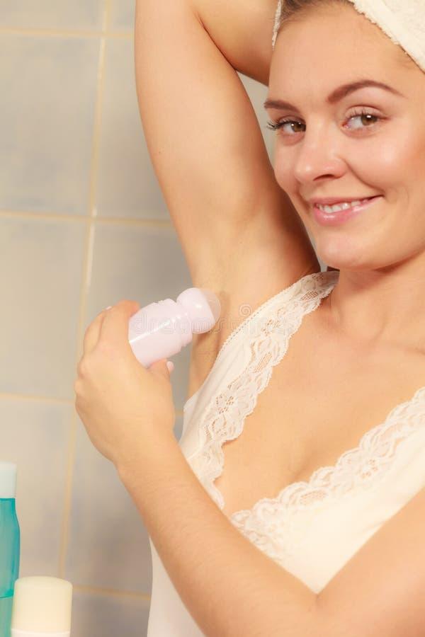 Женщина прикладывая дезодорант ручки в подмышке стоковое фото