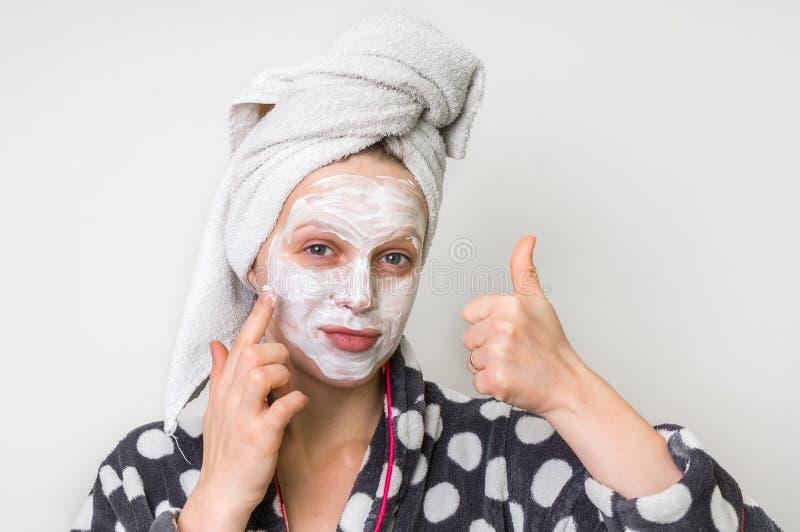Женщина прикладывая естественную лицевую маску от сметаны стоковая фотография