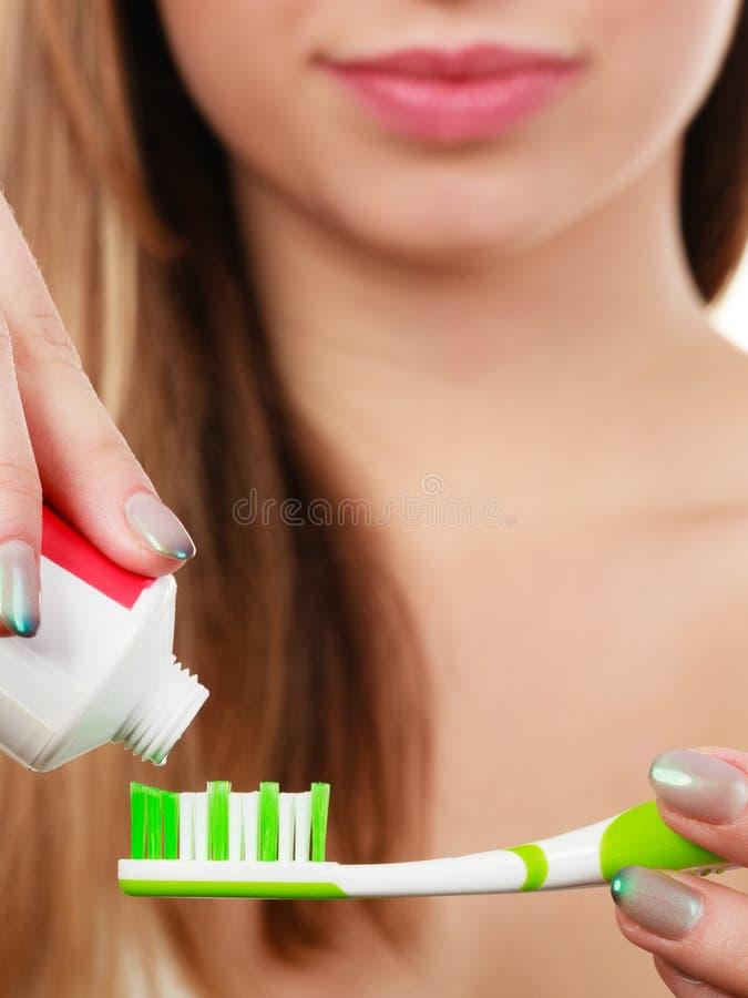 Женщина прикладывая зубную пасту на ее зубной щетке стоковое фото rf