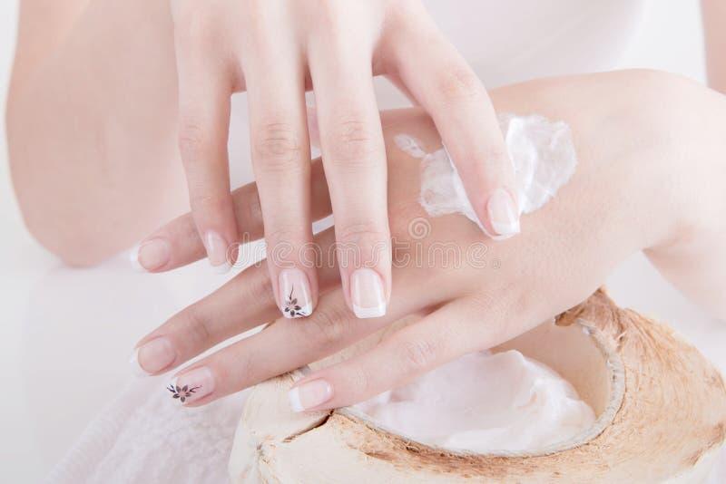 Женщина прикладывая лосьон руки в курорте стоковые фото