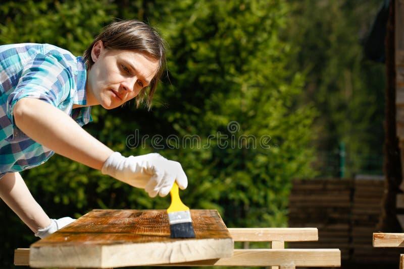 Женщина прикладывая свежую деревянную краску обработки стоковое фото rf