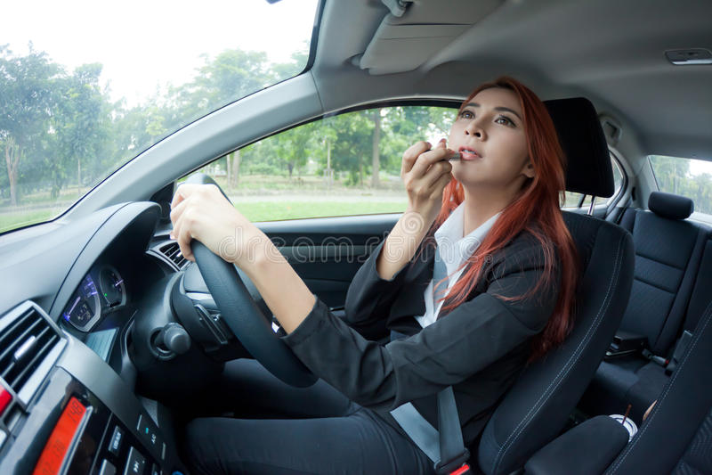 Женщина прикладывая состав пока в автомобиле стоковая фотография rf