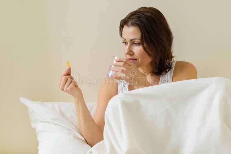 Женщина принимает пилюльку с omega-3 и держать стекло свежей воды в утре кровати Витамин D, e, капсулы рыбьего жира стоковые изображения rf