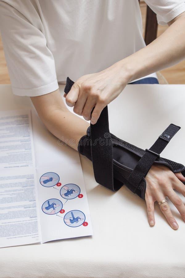 Женщина принимает стабилизатор запястья используя инструкции стоковое фото rf