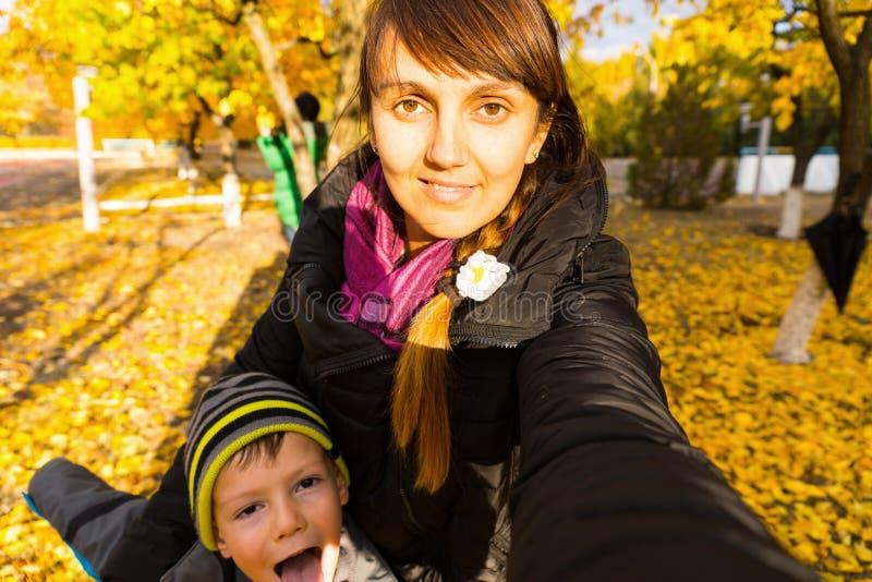 Женщина принимая автопортрет с сыном в парке стоковое фото rf