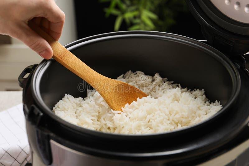Женщина принимая вкусный рис с ложкой от плитаа в кухне стоковое фото rf