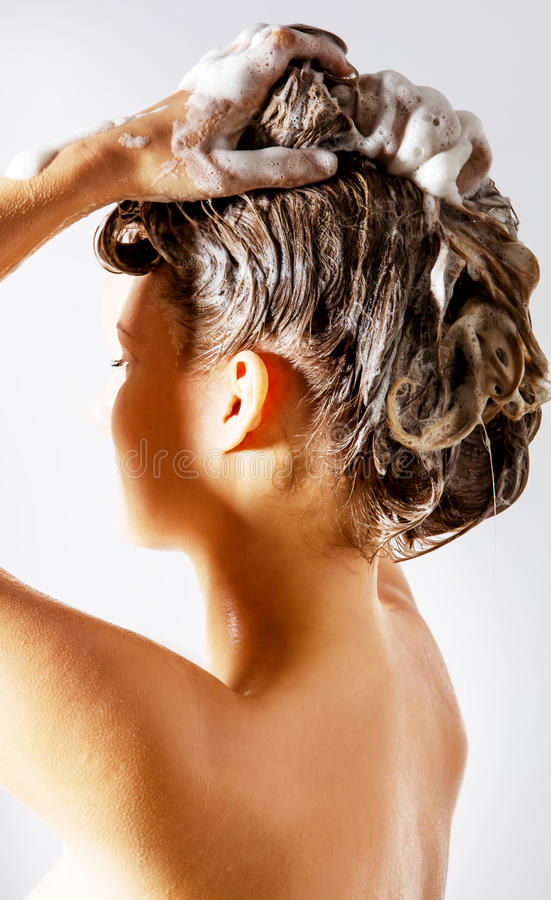 Женщина принимая ливень и shampooing ее волосы Изолировано на белизне стоковое изображение