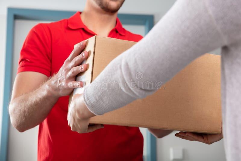 Женщина принимая коробку от работника доставляющего покупки на дом стоковая фотография rf