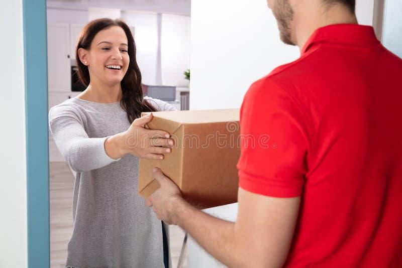 Женщина принимая коробку от работника доставляющего покупки на дом стоковые изображения