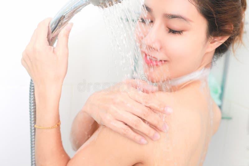Женщина принимая ливень наслаждаясь водой брызгая на ей селективно стоковое изображение rf