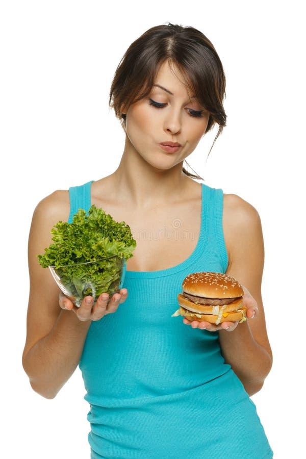 Женщина принимая решениее между здоровыми салатом и быстро-приготовленное питанием стоковые изображения