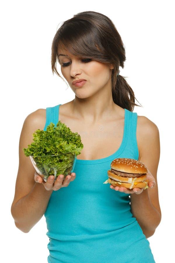 Женщина принимая решениее между здоровыми салатом и быстро-приготовленное питанием стоковые фотографии rf
