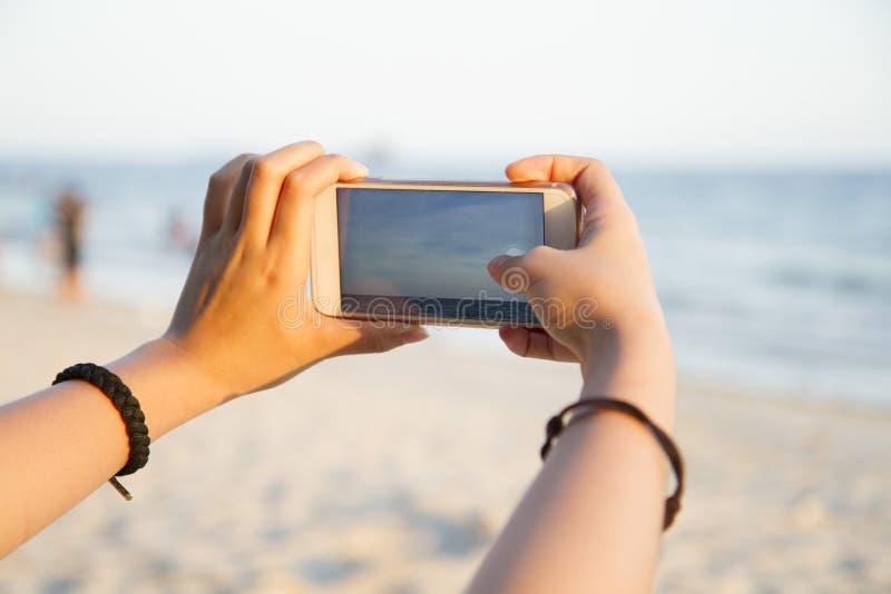 Женщина принимая фото ландшафта пляжа стоковые фото