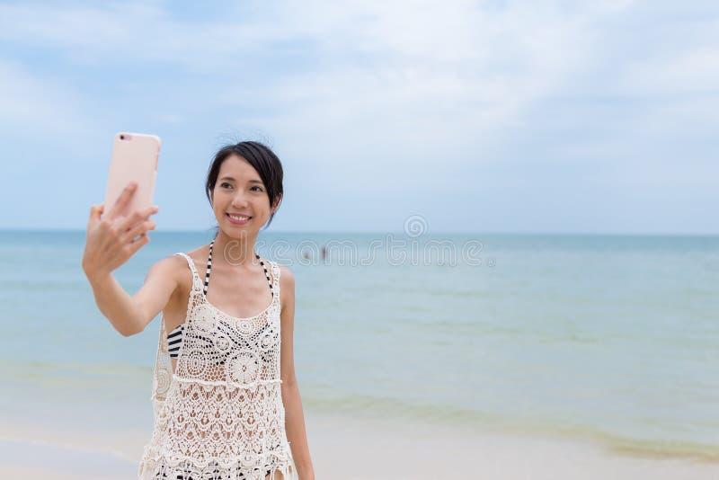 Женщина принимая фото мобильным телефоном в пляже песка стоковое фото