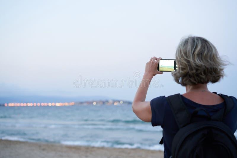 Женщина принимая фото моря по умному телефону на заходе солнца стоковая фотография rf