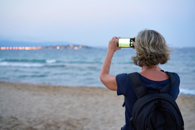 Женщина принимая фото моря по умному телефону на заходе солнца стоковое фото rf