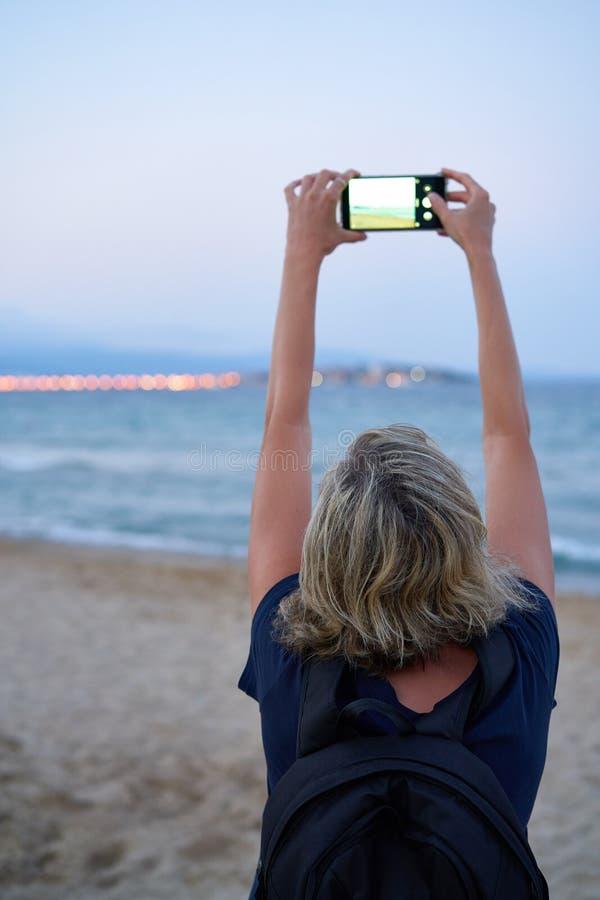 Женщина принимая фото моря по умному телефону на заходе солнца стоковое изображение