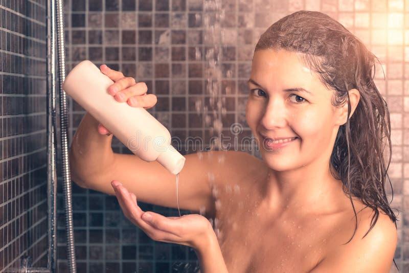 Женщина принимая шампунь волос ливня лить на ее руке стоковые изображения rf