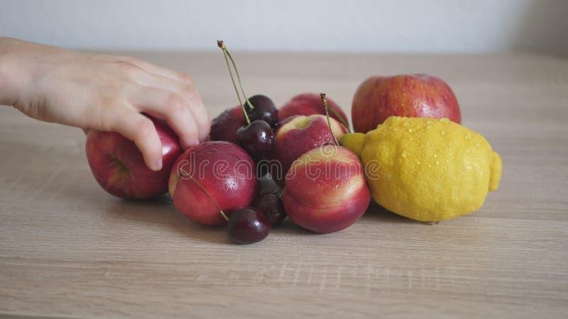 Женщина принимая яблоко от таблицы стоковые изображения rf