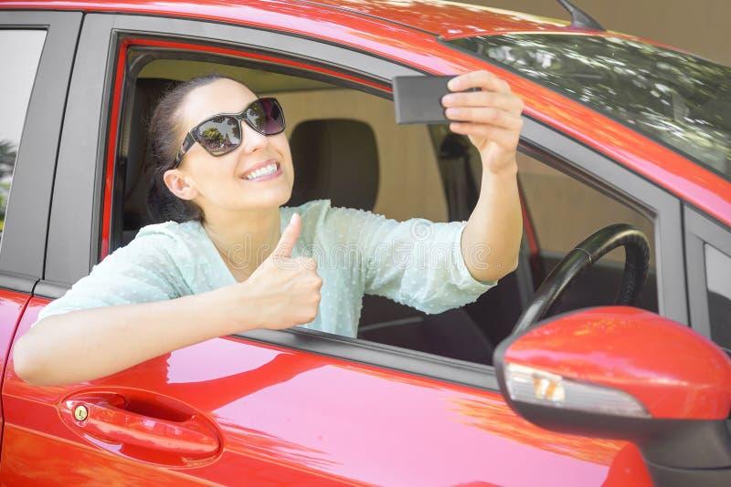 Женщина принимая selfie в автомобиле стоковое фото rf