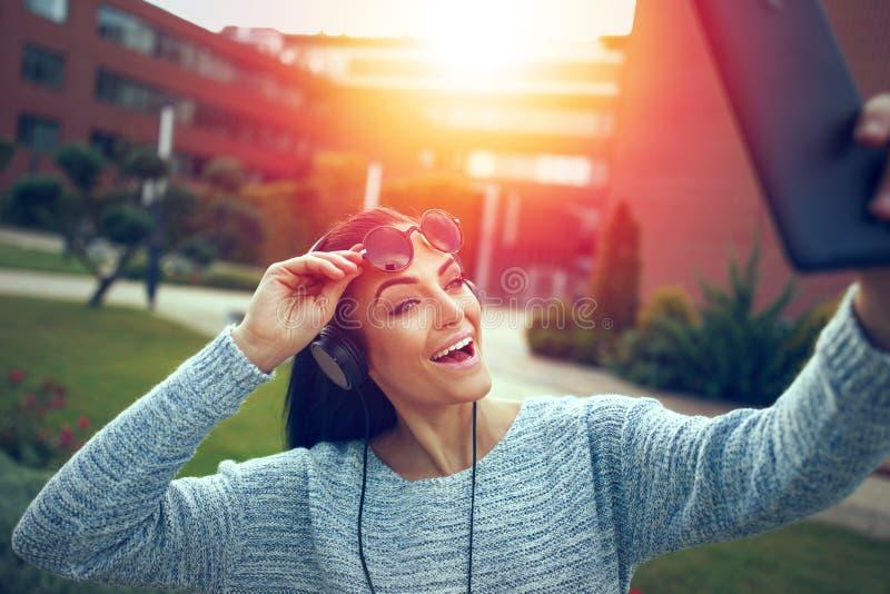 Женщина принимая selfie с таблеткой на парк в заходе солнца стоковые изображения