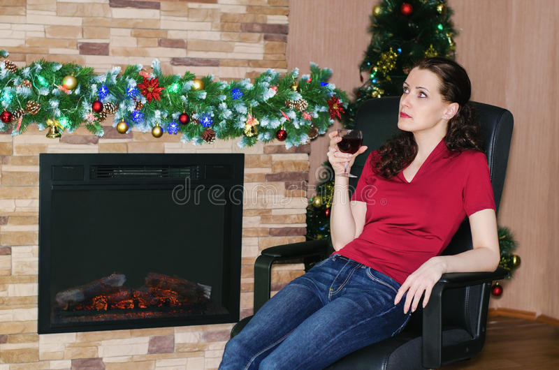 Женщина при бокал вина сидя около камина стоковое изображение rf