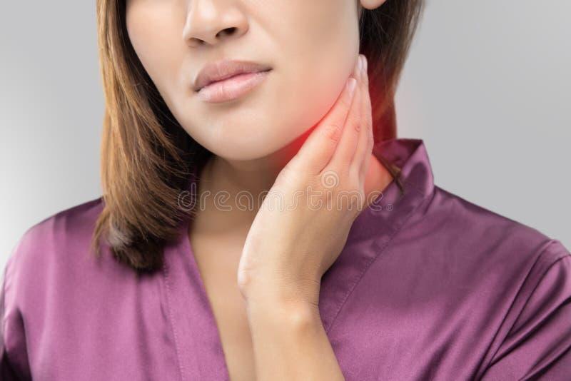 Женщина при боль в горле держа ее шею стоковые фото