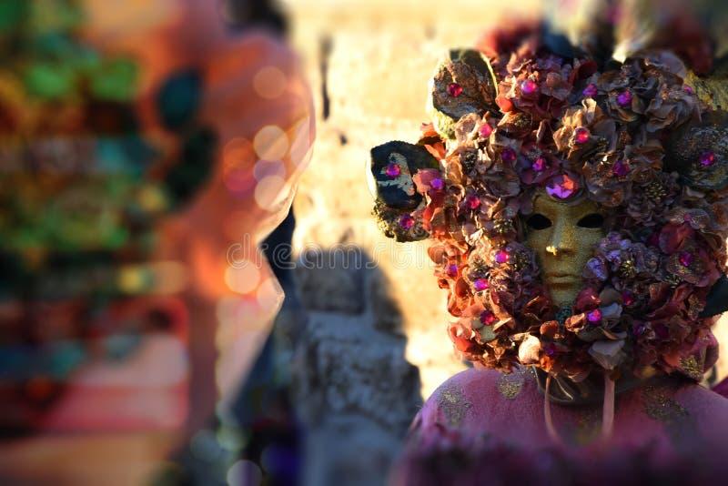 Женщина при венецианская маска украшенная с тканью листового золота и апельсина, каменной предпосылкой стоковое изображение