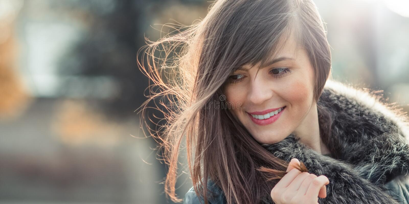 Женщина при волосы дуя в ветре стоковое фото