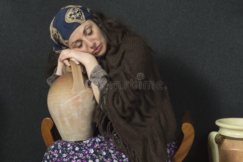 Женщина при ее голова отдыхая на его руках поддерживая амфору стоковая фотография rf
