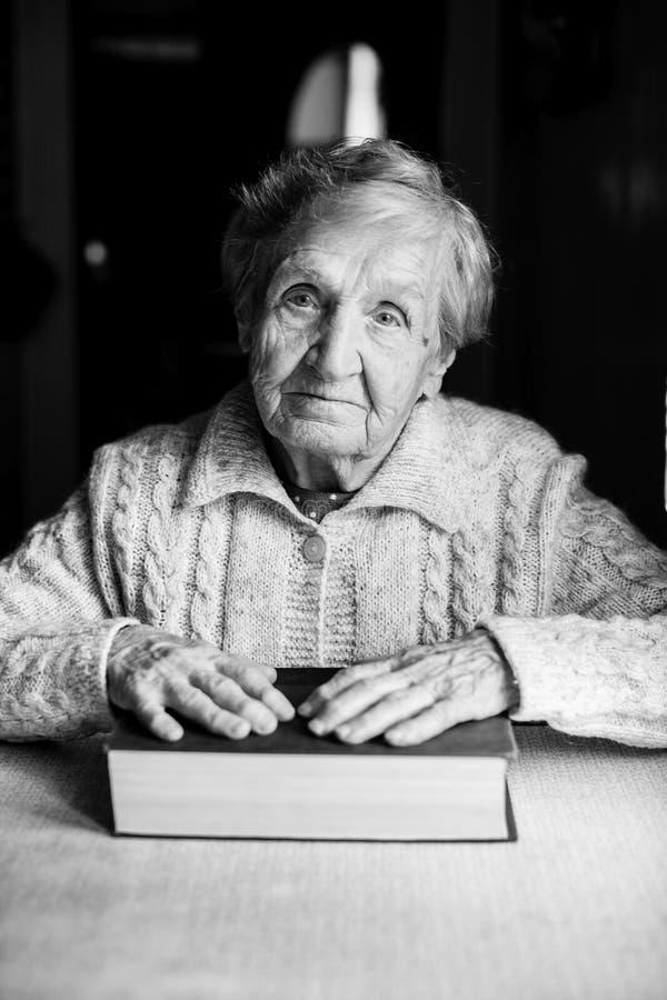 Женщина при закрытая книга сидя на таблице стоковые фото