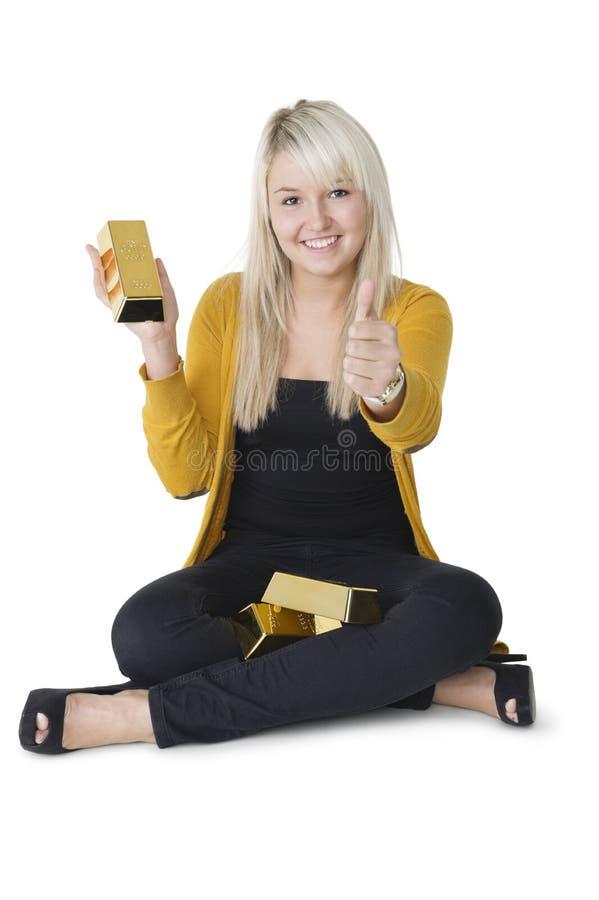 Женщина при золото в слитках давая большие пальцы руки вверх стоковая фотография