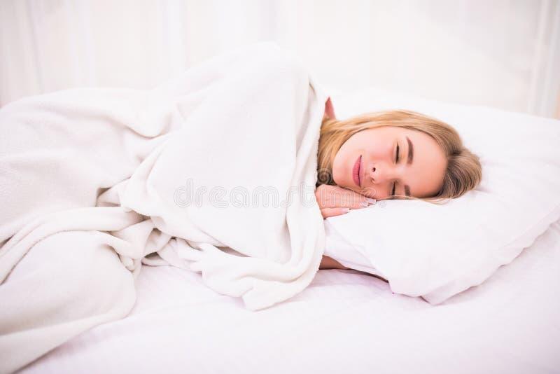 Женщина при длинные белые волосы лежа и спать в кровати стоковая фотография