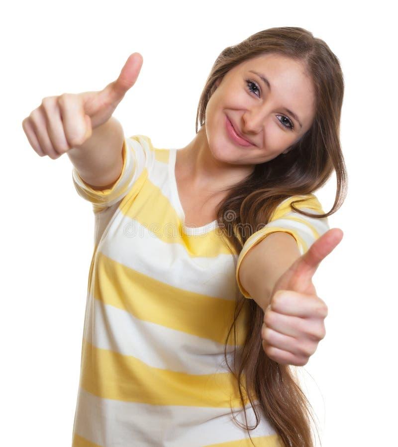 Женщина при длинные коричневые волосы показывая оба большого пальца руки вверх стоковые изображения