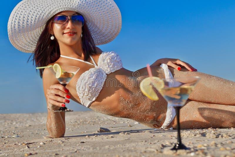 Женщина при коктеил ослабляя на пляже стоковая фотография