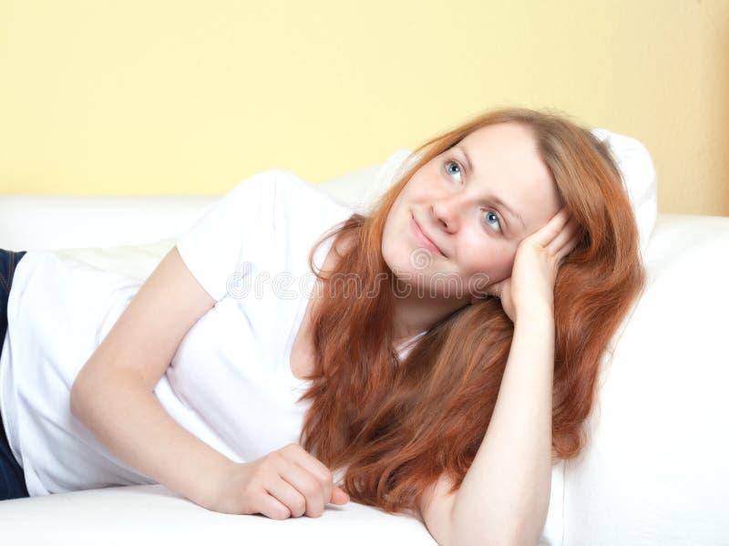 Женщина при красные волосы лежа на софе стоковое фото