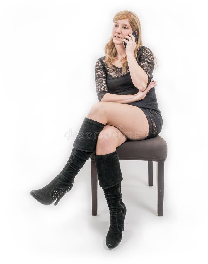 Женщина при мобильный телефон сидя на стуле стоковые фото