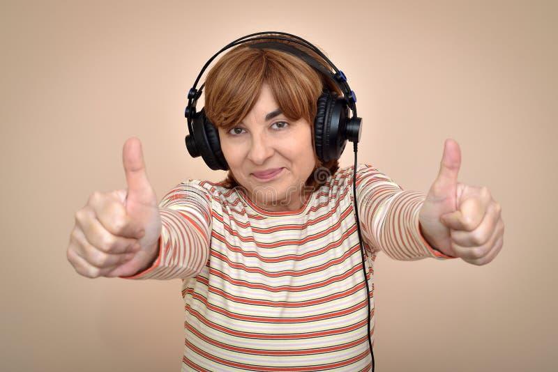 Женщина при наушники показывая большие пальцы руки вверх стоковые изображения