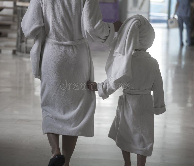Женщина при ребенок в белых купальных халатах идя в спа-центр стоковое фото rf