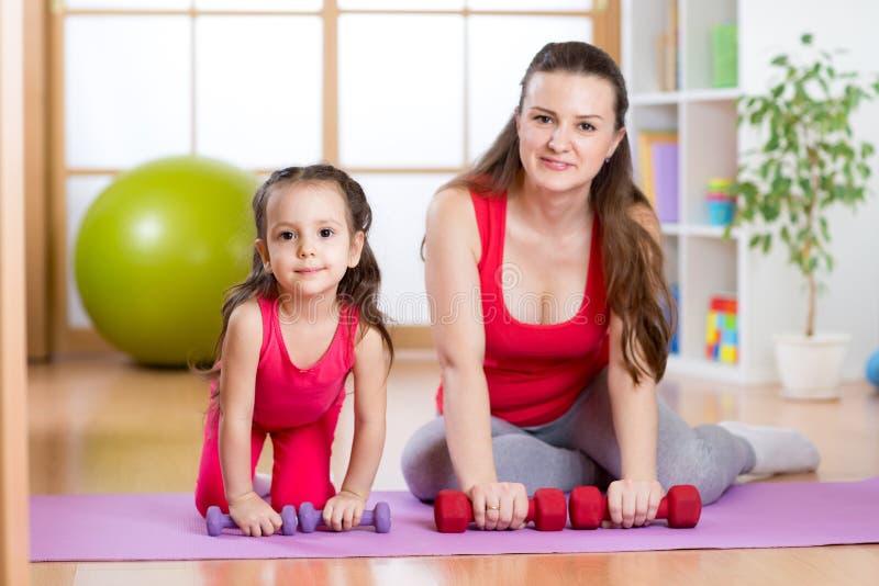 Женщина при ребенок делая гимнастику и фитнес работает стоковые изображения rf